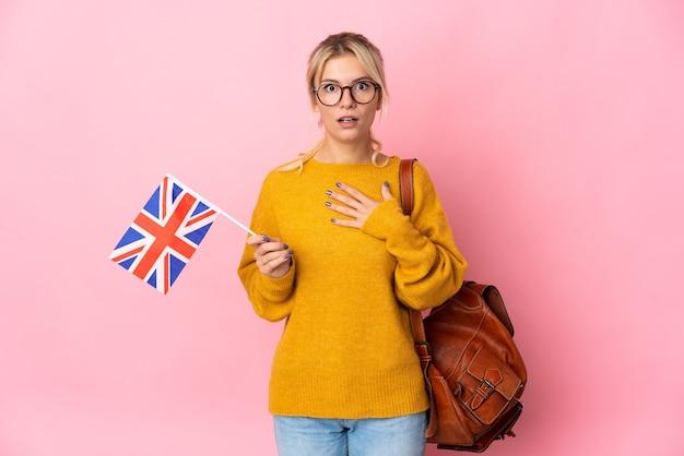 Jovem russa segurando uma bandeira do reino unido isolada em um fundo rosa surpresa e chocada ao olhar para a direita