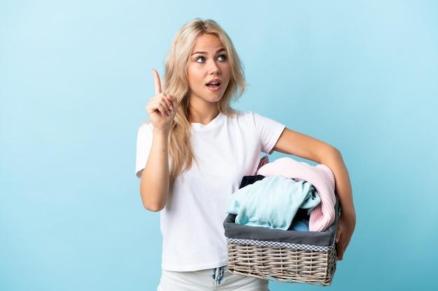 Jovem russa segurando uma cesta de roupas isolada na parede azul com a intenção de perceber a solução enquanto levanta um dedo