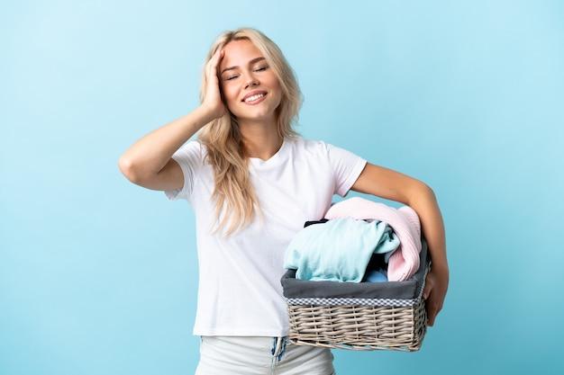 Jovem russa segurando uma cesta de roupas isolada na parede azul e sorrindo muito