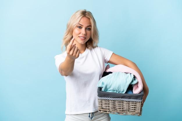 Jovem russa segurando uma cesta de roupas isolada na parede azul fazendo gesto de vir.