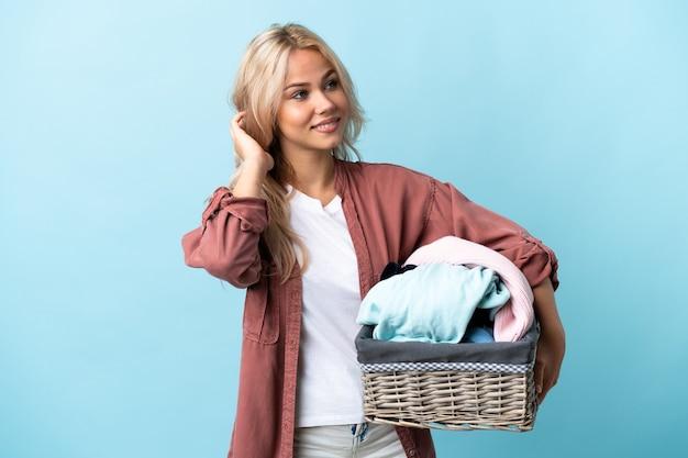 Jovem russa segurando uma cesta de roupas isolada na parede azul, pensando uma ideia
