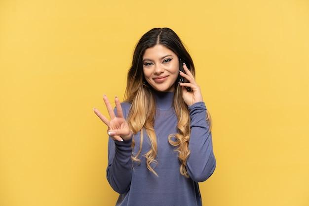 Jovem russa usando telefone celular isolado em um fundo amarelo feliz e contando três com os dedos