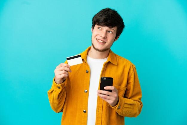 Jovem russo isolado em um fundo azul, comprando com o celular com um cartão de crédito enquanto pensa