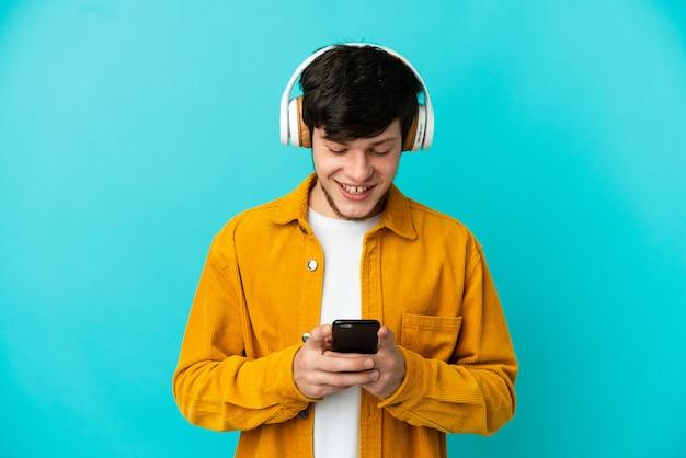 Jovem russo isolado em um fundo azul ouvindo música e olhando para o celular