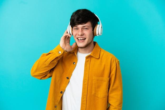 Jovem russo isolado em um fundo azul ouvindo música