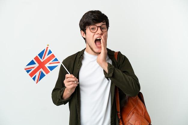 Jovem russo segurando uma bandeira do reino unido, isolada no fundo branco, com expressão facial de surpresa e choque
