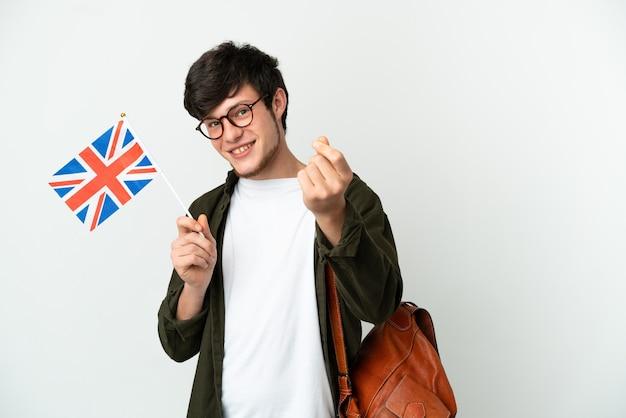 Jovem russo segurando uma bandeira do reino unido, isolada no fundo branco, fazendo gesto de dinheiro