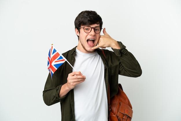 Jovem russo segurando uma bandeira do reino unido, isolada no fundo branco, fazendo gesto de telefone. ligue-me de volta sinal