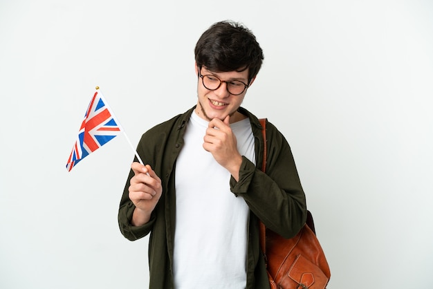 Jovem russo segurando uma bandeira do reino unido, isolada no fundo branco, olhando para o lado e sorrindo