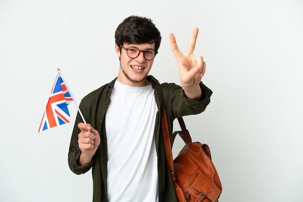 Jovem russo segurando uma bandeira do reino unido, isolada no fundo branco, sorrindo e mostrando o sinal da vitória