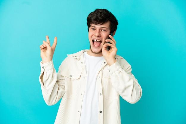 Jovem russo usando telefone celular isolado em fundo azul, sorrindo e mostrando sinal de vitória