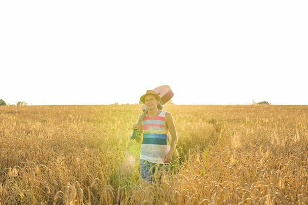 Jovem saindo de casa, cara com violão andando no campo do pôr do sol