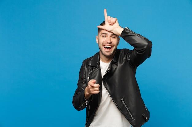 Jovem sarcástico em t-shirt branca de jaqueta preta mostrando sinal de perdedor na testa, apontando para a câmera com sorriso zombeteiro isolado no fundo da parede azul. conceito de estilo de vida de pessoas. simule o espaço da cópia.