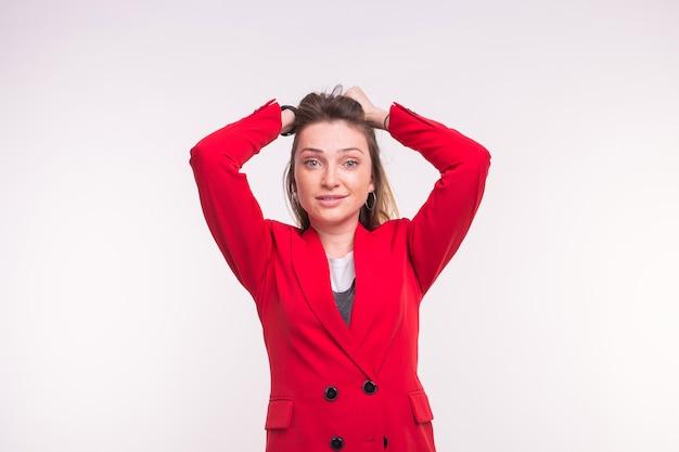 Jovem sardenta surpresa, vestindo terno vermelho sobre fundo branco.