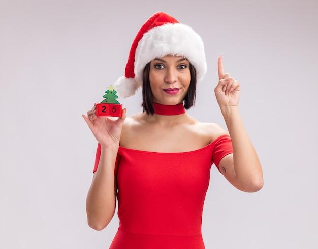 Jovem satisfeita com chapéu de papai noel segurando um brinquedo da árvore de natal e um namorado olhando para a câmera, apontando para cima, isolado no fundo branco