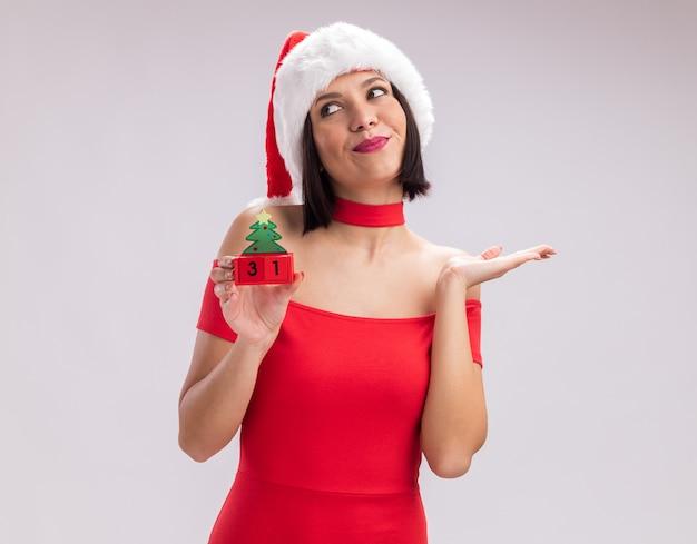 Jovem satisfeita com um chapéu de papai noel segurando um brinquedo da árvore de natal e olhando para o lado, mostrando a mão vazia, isolada no fundo branco