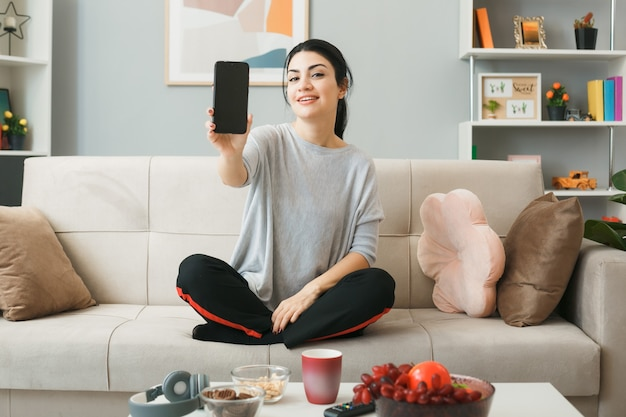 Jovem satisfeita segurando o telefone, sentada no sofá atrás da mesa de centro na sala de estar