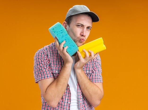 Jovem satisfeito com o limpador de boné segurando uma esponja de limpeza em volta do rosto, isolada na parede laranja
