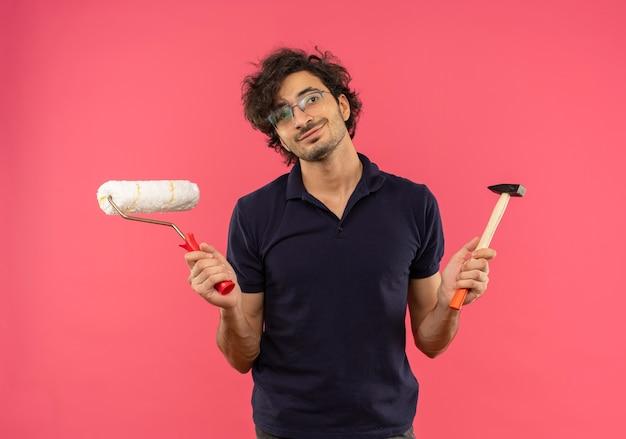Jovem satisfeito com uma camisa preta e óculos ópticos segurando um rolo de pintura e um martelo isolados na parede rosa