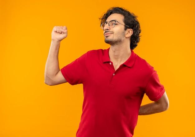 Jovem satisfeito de camisa vermelha com óculos óticos levanta o punho isolado na parede laranja