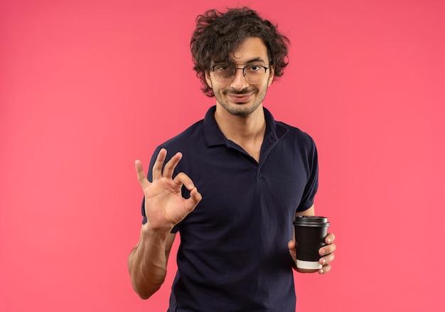 Jovem satisfeito em uma camisa preta com óculos ópticos segurando uma xícara de café e gesticulando com a mão ok sinal isolado na parede rosa