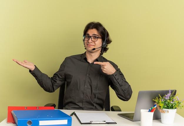 Jovem satisfeito trabalhador de escritório com fones de ouvido e óculos ópticos sentado na mesa com ferramentas de escritório usando laptop aponta para as mãos vazias