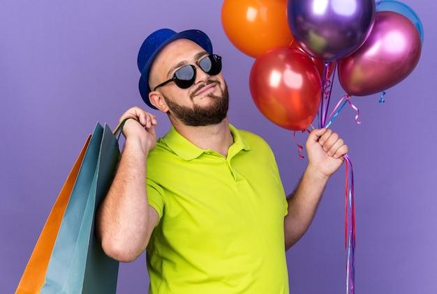 Jovem satisfeito usando chapéu de festa com óculos segurando balões com uma sacola de presente isolada na parede azul