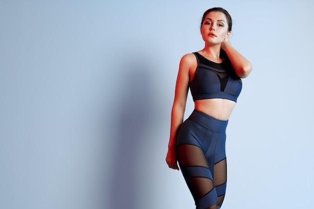 Jovem saudável ajuste no sportswear em pé sobre um fundo cinza