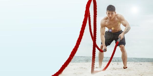 Jovem saudável, atleta fazendo exercício com as cordas na praia. modelo masculino treinando fortemente a parte superior do corpo. conceito de estilo de vida saudável, esporte, fitness, musculação, bem-estar. flyer, copyspace.