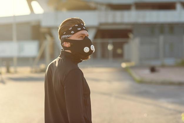 Jovem saudável e bonito correndo no espaço da cidade, o homem usando um respirador para exercícios aeróbicos