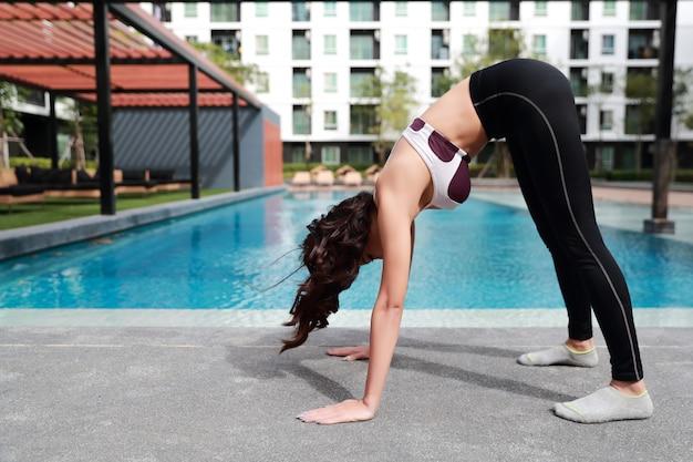 Jovem saudável e desportiva mulher fazer yoga alongamento ao ar livre