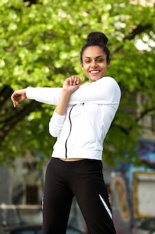 Jovem saudável, fazendo exercícios de alongamento ao ar livre
