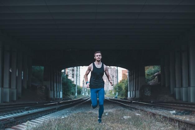 Jovem saudável, movimentando-se na cidade à noite. atleta masculino correndo sob a ponte ao longo dos caminhões da estrada de ferro.