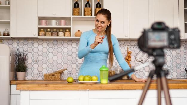 Jovem saudável satisfeita gravando seu episódio de blog de vídeo sobre comida saudável em pé na cozinha em casa. mulher é simpática e sorridente