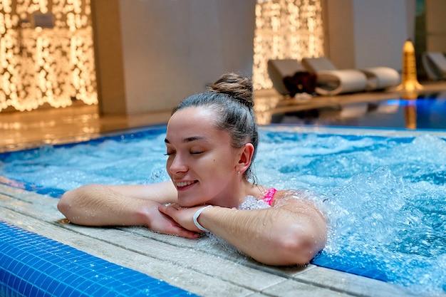 Jovem saudável, uma mulher feliz sonhando com os olhos fechados, relaxando sozinho na banheira no resort spa de bem-estar.