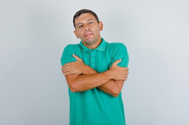 Jovem se abraçando em uma camiseta verde, vista frontal.