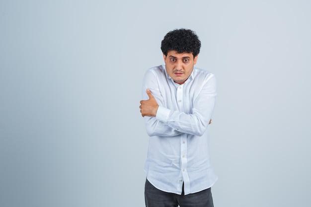 Jovem se abraçando ou sentindo frio em uma camisa branca e parecendo desamparado. vista frontal.