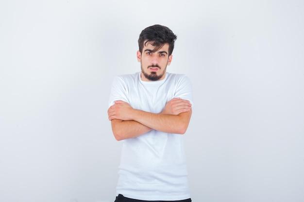Jovem se abraçando ou sentindo frio em uma camiseta branca e parecendo sensato