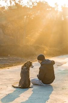 Jovem se divertindo com seu cachorro na natureza com os raios do sol da manhã ama meu cachorro