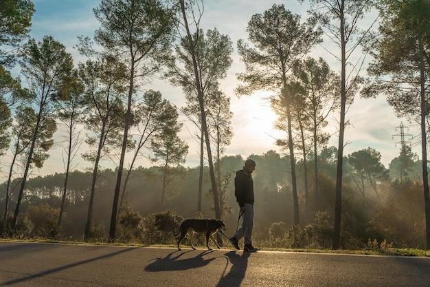 Jovem se divertindo com seu cachorro na natureza com os raios do sol da manhã quente.
