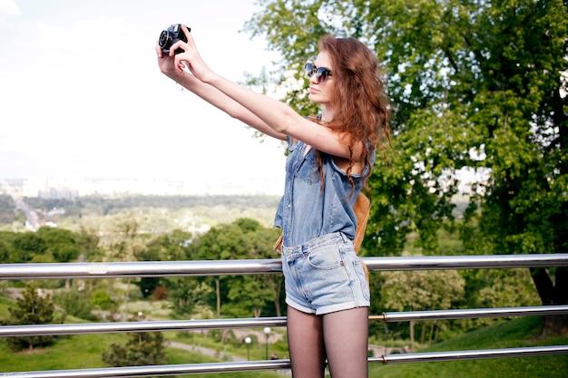 Jovem se divertindo na natureza e tirando fotos