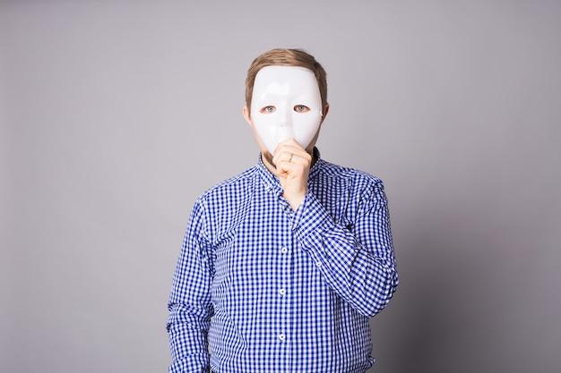 Jovem se escondendo atrás de uma máscara branca em uma parede cinza.