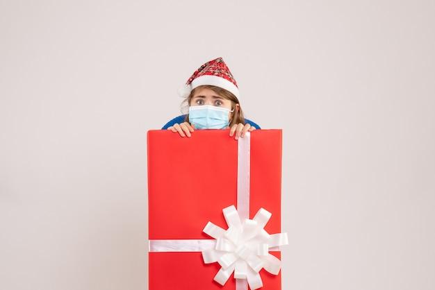 Jovem se escondendo dentro de uma caixa de presente com máscara em branco