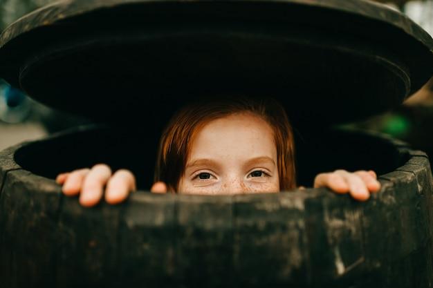 Jovem se escondendo em um barril de madeira