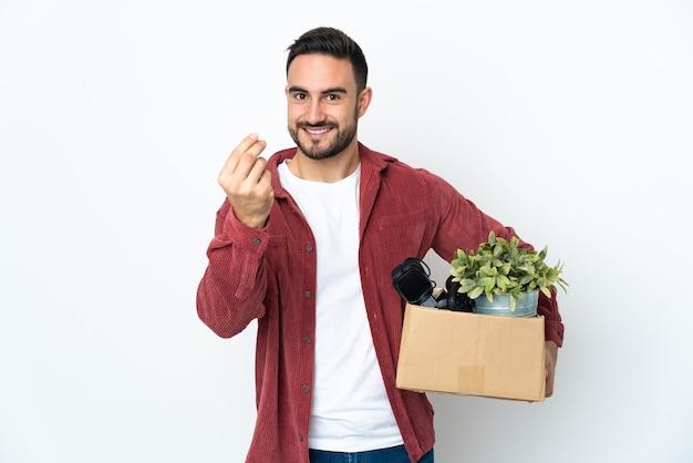Jovem se mexendo enquanto pega uma caixa cheia de coisas isoladas na parede branca fazendo gesto de dinheiro