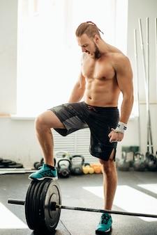 Jovem se preparando para o treinamento de barra no ginásio. colocou a perna na barra