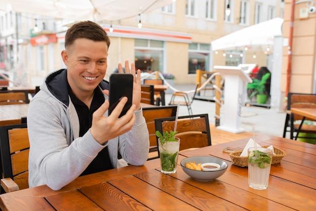 Jovem se senta à mesa de um café de rua e se comunica emocionalmente por vídeo comunicação