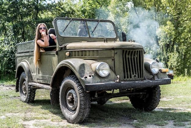 Jovem se senta em um carro militar.