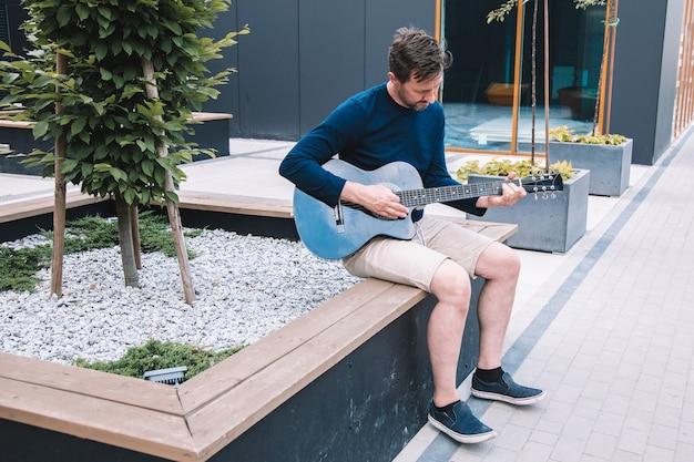 Jovem se senta no banco de concreto incity square e toca guitarra. estilo de vida. foto de alta qualidade