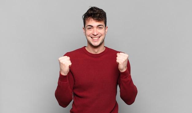 Jovem se sentindo chocado, animado e feliz, rindo e comemorando o sucesso, dizendo uau!